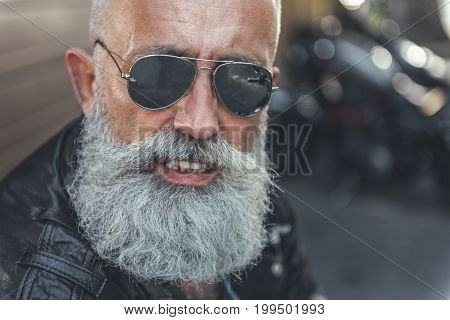 Joyous old bearded biker wearing goggles. He glancing at camera with smile. Portrait. copy space