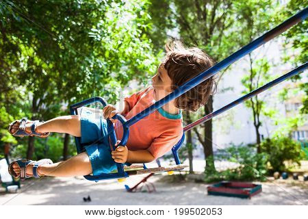 Child Is Having Fun On The Swing.