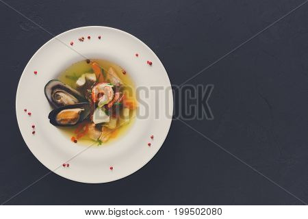 French cuisine restaurant. Seafood soup with white fish, shrimps and mussels in plate sprinkled with spices. Freshly cooked exclusive meals at black background with copy space, top view
