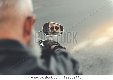 Interested old bearded biker is looking at focus mirror. He touching to his moustache. Top view. Copy space on right side