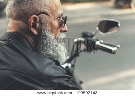 Aged bearded biker in sunglasses is sitting at motorcycle and looking aside. He wearing jacket made of black leather. Focus on face. Profile