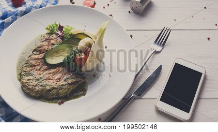 Business lunch at restaurant. Grilled black angus steak with vegetables in fennel and green pepper sauce. Healthy food, served on round plate at white wood background and checkered cloth and mobile