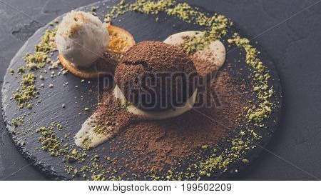 Exquisite dessert on black background. Chocolate fondant, creme anglaise and vanilla ice cream, sprinkled with cocoa on slate decorated with orange citron and pistachio crumble, closeup, copy space