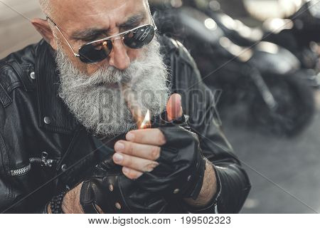 Elder bearded biker in goggles is wearing black clothes made from leather. He setting cigar on fire. Portrait