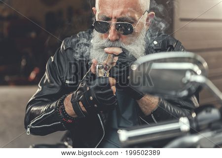 Busy old bearded biker is setting cigar on fire by lighter. He sitting at motorbike and wearing leather clothes. Portrait