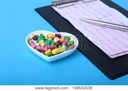 RX prescription and colorful assortment pills and capsules on plate