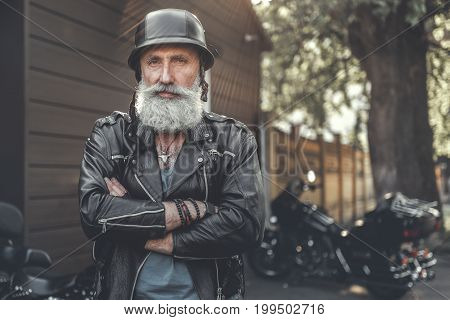 Glad aged bearded biker wearing leather jacket is standing near motorbikes. He crossing hands and looking at camera with smile. Portrait. Copy space