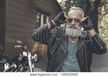 Old bearded biker is putting goggles at face. He standing near garage and motorbikes. Portrait