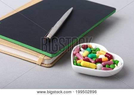 notebook and colorful assortment pills, capsules on plate