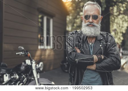 Confident bearded aged spectacled biker is crossing his hands and looking at camera. He standing nearby motorbike. Portrait