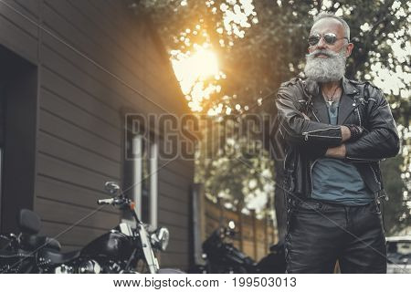 Confident bearded elder biker wearing goggles is standing afore his motorbike and crossing hands. Low angle. Copy space on left side