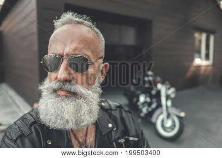 Confident old biker is wearing black leather jacket and looking aside with serious face. He standing afore motorcycle. Portrait. copy space on right side