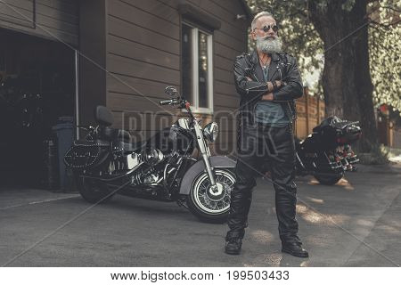 Confident mature bearded biker wearing clothes made from leather is standing afore motorcycle. He crossing hands. Full length portrait