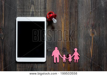 Mockup for adoption concept. Tablet PC on dark wooden background top view.