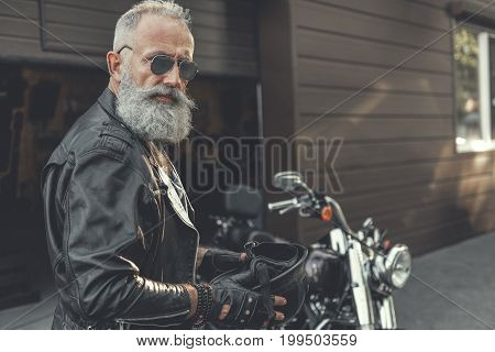 Assured aged bearded biker is holding slam. He spectacled standing near motorcycle and turning to camera. Portrait