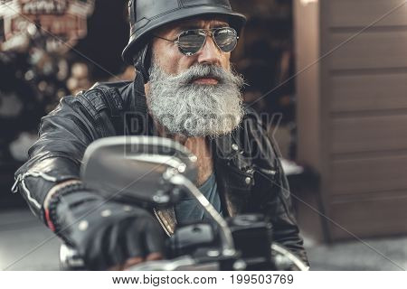 Attentive mature bearded biker is going to move forward on his motorcycle. He wearing helmet and goggles. Portrait