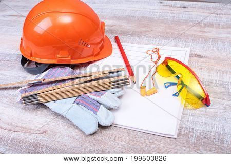 Orange hard hat, earplug, safety glasses and gloves for work. Earplug to reduce noise on a white background