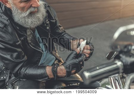 Concentrated old bearded biker is sitting on motorcycle and using small knife. Top view. Close up pf hiis hands