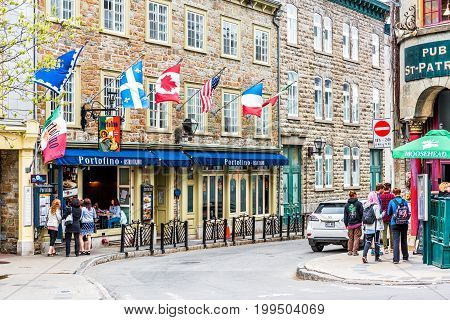 Quebec City Canada - May 29 2017: Old town street Rue Couillard with flags by Portofino restaurant and people walking