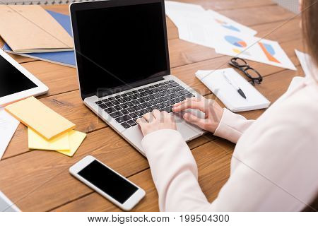 Business woman typing on laptop with blank screen, copy space