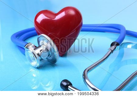 Medical stethoscope and red heart isolated on mirror background
