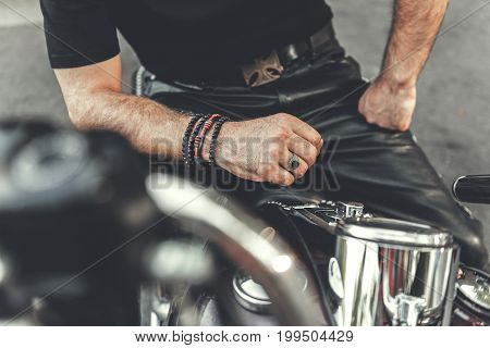 Mature biker wearing leather trousers is sitting at motorbike. Focus on male arms and shiny fuel tank. Close up