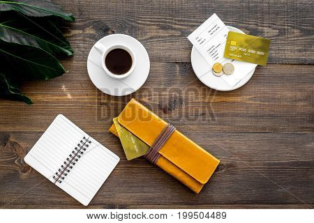 Pay in the restaurant. Purse, bill and bank card near cup of coffee on dark wooden table top view.