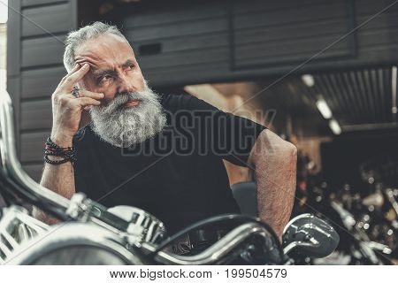 Serious mature bearded biker is sitting at motorcycle and glancing aside with wistfulness in sight. Portrait