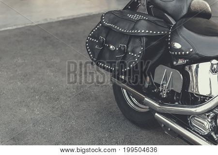 Convenient black bag made of leather is affixed to modern motorcycle. Polished details of well-groomed vehicle. Close up. Copy space
