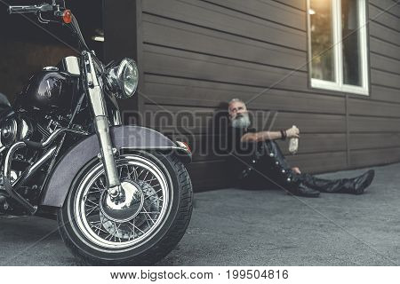 Tired bearded elder biker is leaning against wall and holding bottle. He looking at his motorbike. Focus on shiny vehicle