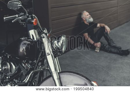 Mindful old bearded biker is sitting near wall and keeping bottle of alcohol. Focus on well-groomed motorcycle
