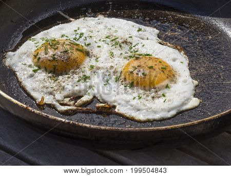 Two Fried Eggs Sunny Side Up Egg On Old Scratched Pan