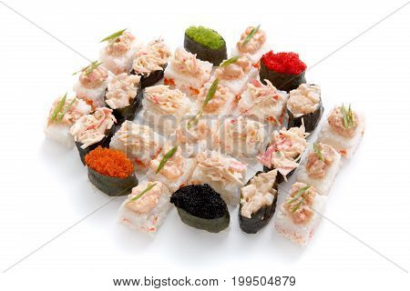 Big party sushi set isolated on white background. Japanese food delivery and take away. Fish rolls with snow crab meat on top and spicy gunkans with colorful tobiko