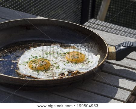 Two Fried Eggs Sunny Side Up Egg On Old Pan On Wooden Table