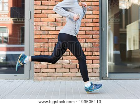 Unrecognizable woman running in city near brick building with mirror windows, copy space, side view