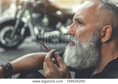 Thoughtful elder bearded biker is sitting. He smoking cigar and looking ahead with bewilderment. Portrait