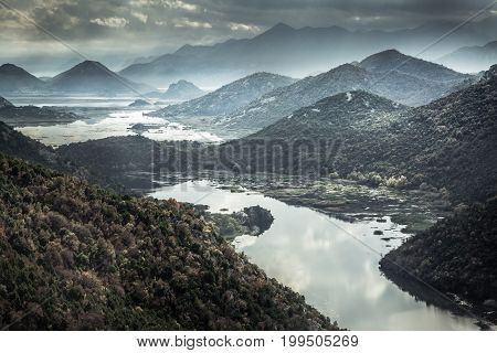 Mountains landscape with river creek around Rijeka Crnojevica river from high view in overcast day with dramatic sky in Europe country Montenegro