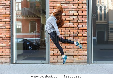 Beautiful young woman jumping against brick wall, copy space. Freedom spirit concept