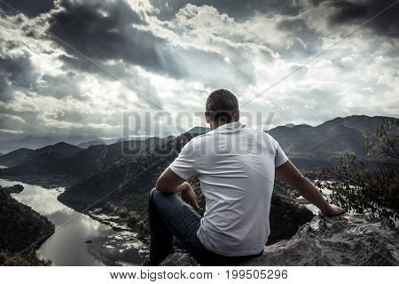 Lonely man looking with hope at horizon on mountain peak with dramatic sunlight during sunset with effect of light at the end of tunnel