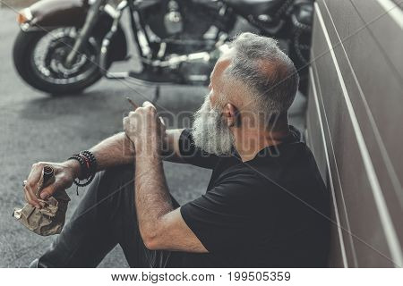 Mature bearded biker is sitting near wall and looking at his motorcycle. He holding alcohol. Top view