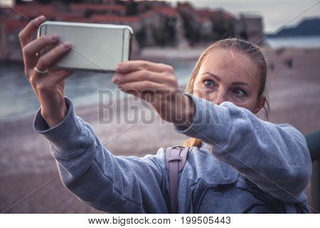 Woman traveler making selfie mobile photo on smart phone during travel holidays at beach for social media networking