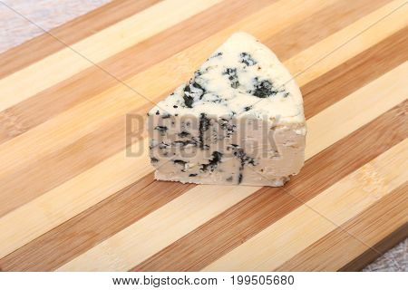 Plate with Tasty blue cheese on wooden table.
