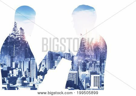 Young businessmen silhouettes discussing contract on abstract city background with sunlight. Meeting concept. Double exposure
