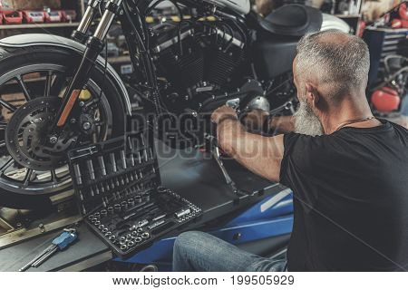 Aged biker is sitting near motorcycle and making repairments. Various instruments are in open box. Focus on his back