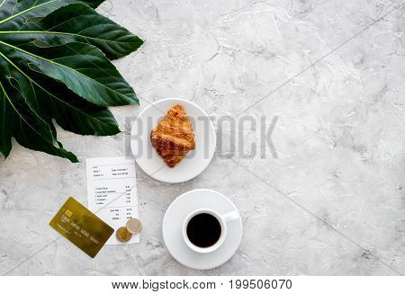 Restaurant bill and bank card near cup of coffee and croissant on grey stone table top view.