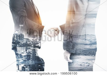 Side view of handshake on abstract city background. Partnership concept. Double exposure