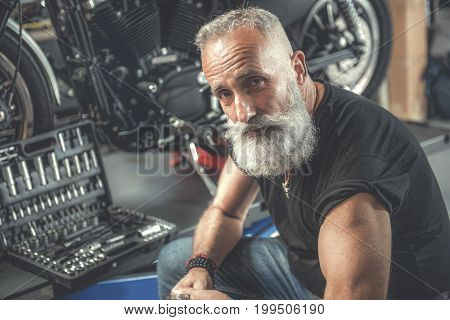 Confident mature bearded biker is sitting near motorbike and looking at camera. Box, full of tools on stand. Portrait