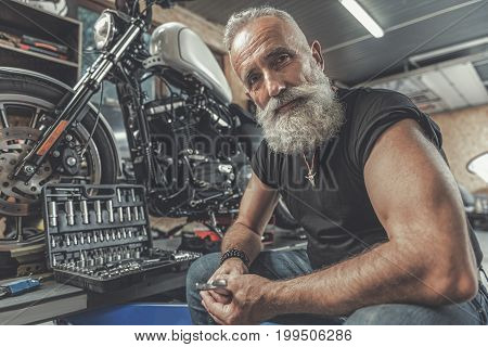 Sincere aged bearded biker is holding wrench and glancing at camera with smile. He sitting in garage near motorcycle. Portrait. Low angle