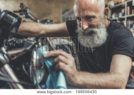 Joyous bearded mature biker is squatting near motorcycle and polishing spotlight with wide smile. He working in garage. Portrait