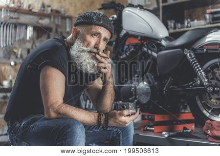Thoughtful mature bearded biker is sitting at garage near motor bike and smoking cigarette. He glancing ahead with serious face. Portrait